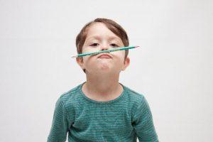 鉛筆を口に乗せる少年