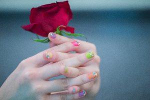 ネイルした指とバラ